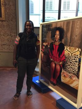 Mickalene Thomas poses before the portrait of her mother.